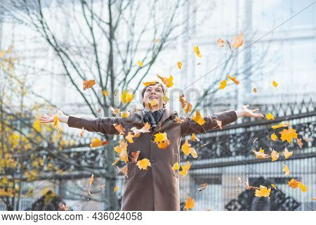 A Businessman Man In A Brown Coat And Scarf Threw Bright Autumn Yellow Maple Leaves, Spreading His A