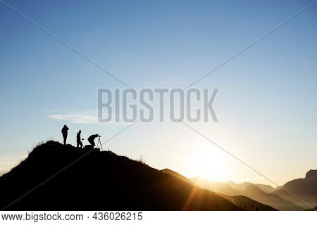 Group of photographers taking pictures at sunset in the Dolomites, Passo Giau, Italy, Europe