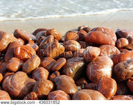 Unique Red Jasper Beach. Many Pieces Of Red Jasper Polished By The Sea. Wet Sea Stones On A Blurred