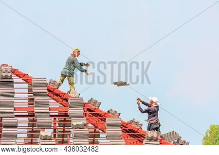 Construction Roofer Installing Roof Tiles At House Building Site