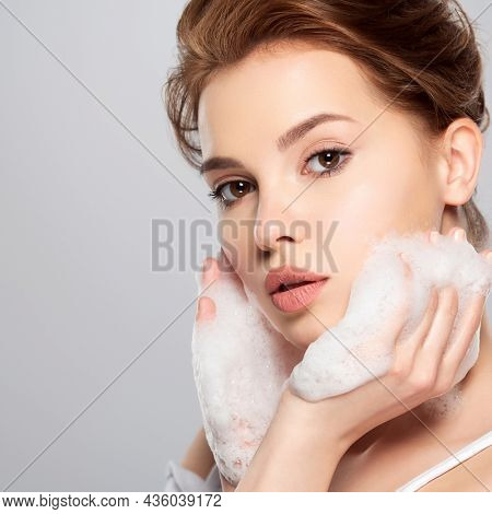Girl moistens her face.   Woman with soap foam street. Beautiful face of young caucasian woman with perfect healthy skin, isolated.   Pretty white model caring of face. Skin care concept.