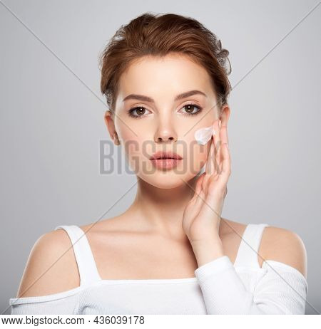 Spot of cosmetic cream on a woman's face. Beautiful face of young caucasian woman with perfect healthy skin, isolated.   Pretty white model caring of face.  Woman applying cream on face.