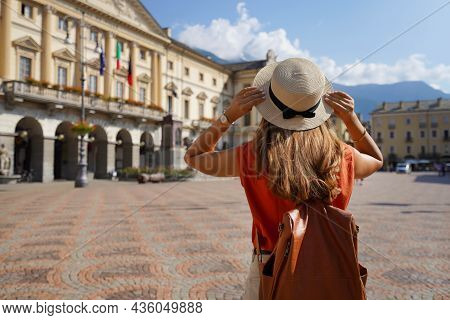 Stylish Traveler Woman Holds Hat On Sunny Day In Aosta City, Italy