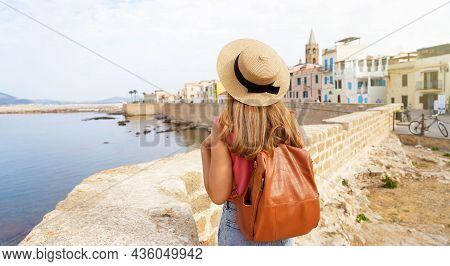 Tourism In Sardinia. Panoramic Banner View Of Young Woman With Hat And Backpack In Alghero Old Town,