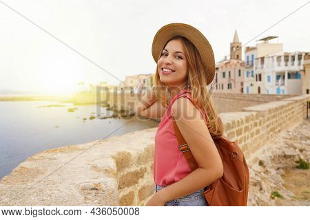 Portrait Of Smiling Relaxed Traveler Woman Walking Along Alghero Seafront, Sardinia, Italy