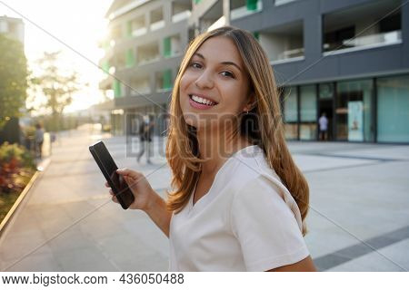 Side View Of Beauty Happy Woman Looking At Camera With Phone In City