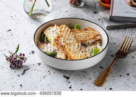 Bowl Of Chicken Caesar Salad On Light Background
