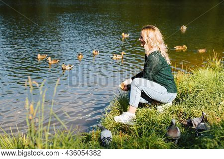 Side View Of Happy Young Woman Sitting On Shore Of Lake And Feeding Ducks In Nature. Beautiful Smili