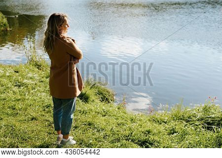 Side View Of Lonely Smiling Young Woman Standing On Shore Near Water And Contemplating, Enjoying, Be