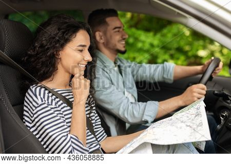 Happy Middle-eastern Lovers Going Vacation By Car, Looking At Map