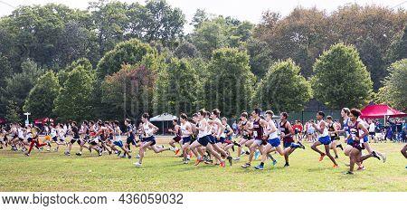 Bronx, New York, Usa - 9 October 2021: Side View Of High School Boys Running Across A Grass Field At