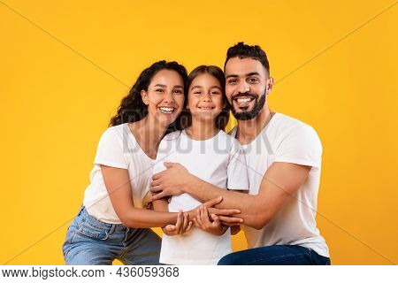 Happy Middle-eastern Parents Hugging Their Kid Daughter On Yellow Background