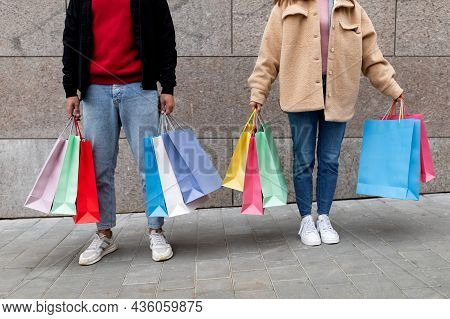 Unrecognizable Young Couple Holding Shopper Bags, Posing In Front Of Stone Wall Outdoors, Going Shop