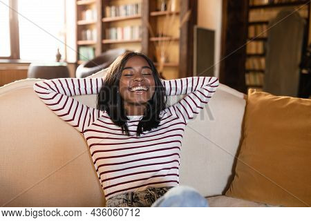 Cheerful Young Black Woman Resting On Cozy Couch With Closed Eyes, Holding Hands Behind Her Head, Na