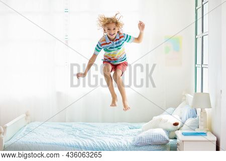 Child Jumping On Bed In White Bedroom With Big Window. Kids Play At Home. Fun Jump On Parents Bed.