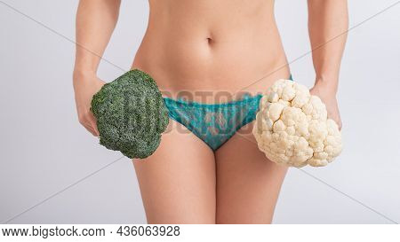 A Faceless Woman In Panties Holds Cauliflower And Broccoli On A White Background. Food Habits.