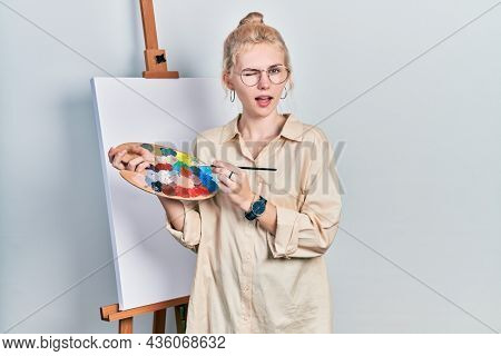 Beautiful caucasian woman with blond hair standing drawing with palette by painter easel stand winking looking at the camera with sexy expression, cheerful and happy face.
