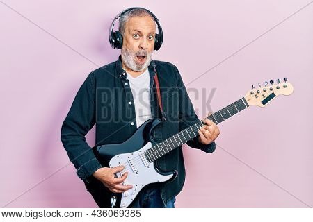 Handsome senior man with beard playing electric guitar in shock face, looking skeptical and sarcastic, surprised with open mouth