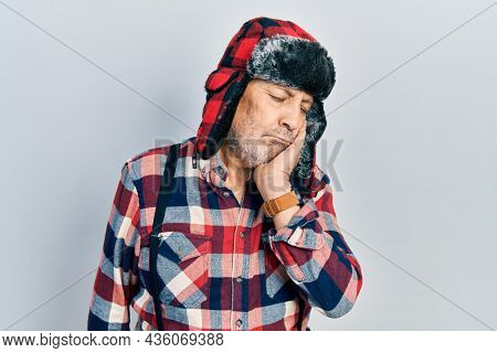 Handsome mature man wearing winter hat with ear flaps thinking looking tired and bored with depression problems with crossed arms.