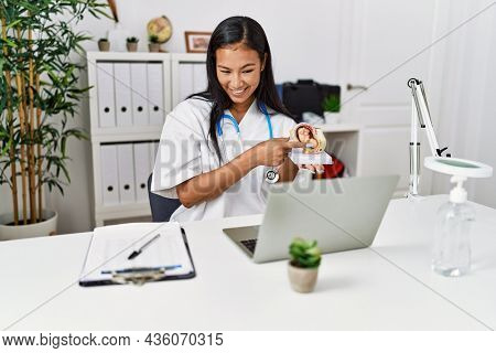 Young latin woman holding anatomical model of uterus having video call at clinic