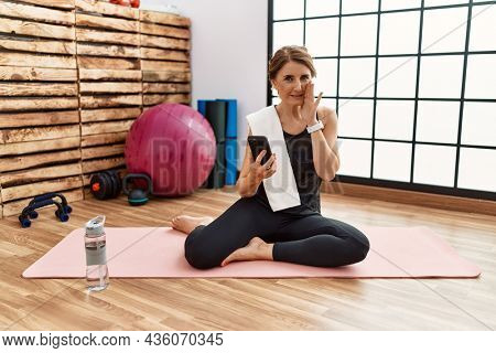 Middle age woman sitting on training mat at the gym using smartphone hand on mouth telling secret rumor, whispering malicious talk conversation