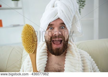 Portrait Of Funny Guy Wear Turban Towel Holding In Hands Massage Brush While Sits On Sofa. Male Skin