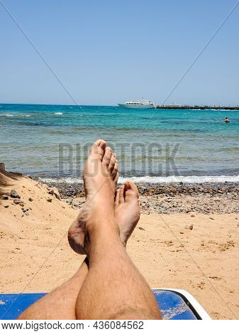 Close-up Of Mens Legs Against The Background Of The Sea. The Concept Of Recreation, A Man Sunbathing