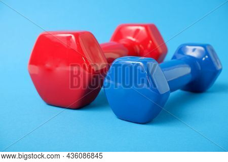 Simple Dumbbell. Blue And Red Dumbbells For Fitness On A Blue Background.