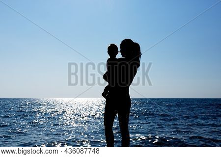 A Young Girl Holds A Child In Her Arms Against The Sun. Silhouette Photography. High Quality Photo