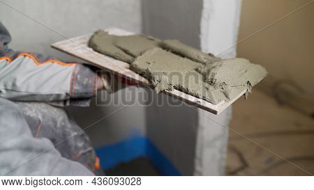 A Worker Applies The Mortar To The Tile For Laying The Tiles. Worker Applies Glue To Ceramic Tile. W