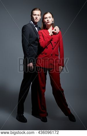 Full length portrait of a stunning beautiful couple of young people in elegant pantsuits on a dark gray background in the studio. Impeccable look. Evening fashion. Men's clothing style.