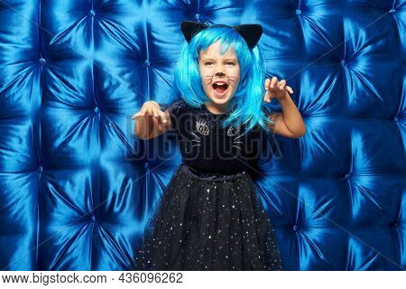 Carnival kitty costume. Cute little girl in a cat costume and bright blue wig shouts and scares with her hands at a Halloween party. Bright blue background.