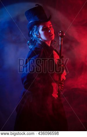 Refined elegant young 19th century lady enchanted by dark mysterious forces stands in the background of a huge moon with gloomy red light and fog around. Halloween. Vampires.