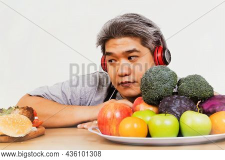 Fat Asian Man Trying To Lose Weight, Hesitant To Eat Healthy Fruits And Vegetables : Man Who Glanced