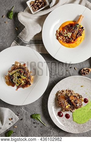 Set with main courses. Composition with meat dishes on gray stone table and textile in contemporary style. Roasted beef tongue with pearl barley; beef cheeks and leg of lamb in restaurant menu