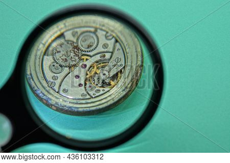 Black Magnifying Glass Magnifies The Gray Metal Mechanism Of An Old Clock On A Green Table