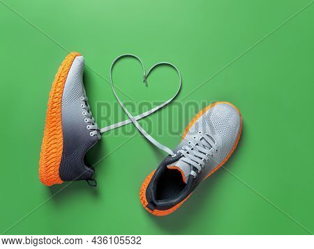 Shoelace Heart Symbol Between Gray Textile Sneakers With Grooved Orange Sole On Grassy Green Backgro