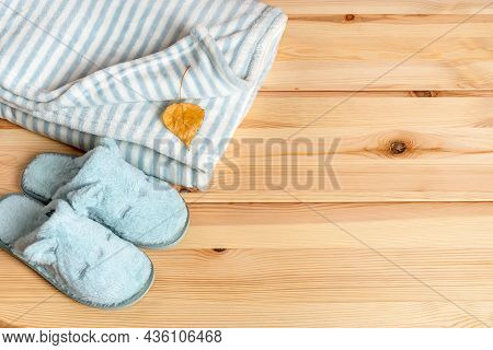 Yellow Autumn Leaf Over Striped Fuzzy Blanket And Funny Cat Face Blue Slippers Over Natural Wood Sur