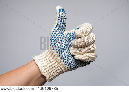 Hand Of A Builder, Worker Wearing Construction Safety Protection Glove Showing Gesture Thumb Up.