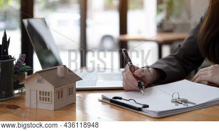 Real Estate Realtor Working In The Office, Reviewing Rental Contract On Papers. Property Consultant