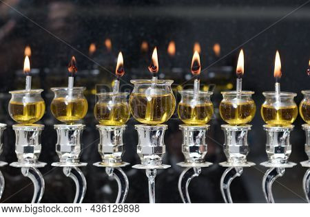 Hanukkah Candles Are Lit In A Silver Menorah Against The Backdrop Of The Darkness Of The Night