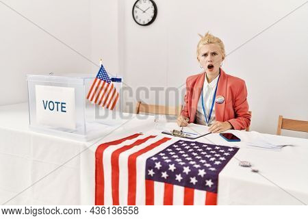 Beautiful caucasian woman working at political campaign in shock face, looking skeptical and sarcastic, surprised with open mouth