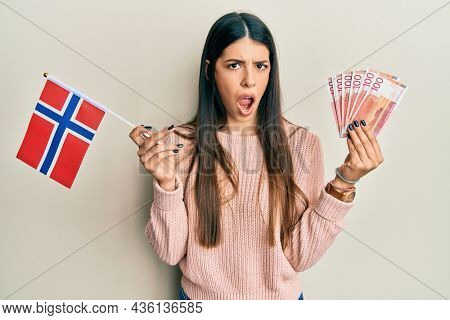 Young hispanic woman holding norway flag and krone banknotes in shock face, looking skeptical and sarcastic, surprised with open mouth