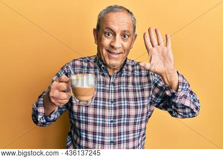Handsome senior man with grey hair drinking a cup coffee waiving saying hello happy and smiling, friendly welcome gesture