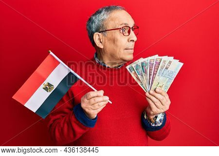 Handsome senior man with grey hair holding egypt flag and egyptian pounds banknotes smiling looking to the side and staring away thinking.