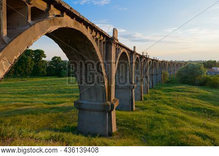 A Long Old Arched Railway Bridge Over A Green Ravine On A Summer Evening