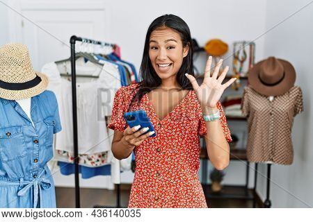 Young hispanic woman working at retail boutique using smartphone waiving saying hello happy and smiling, friendly welcome gesture