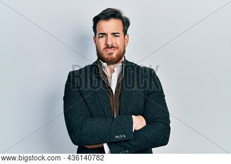 Handsome caucasian man with beard with arms crossed gesture clueless and confused expression. doubt concept.