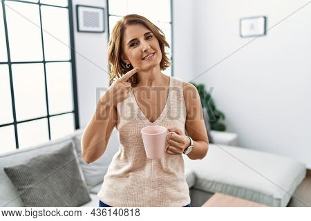 Middle age woman drinking a cup coffee at home smiling cheerful showing and pointing with fingers teeth and mouth. dental health concept.
