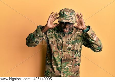 Young african american man wearing army uniform trying to hear both hands on ear gesture, curious for gossip. hearing problem, deaf